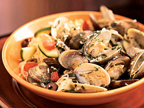 Littleneck clams are easily found at most supermarket seafood counters, and can be quite inexpensive. They're also quick to cook, which makes them an excellent but unexpected choice for a weeknight dinner. Seasoned simply with lemon, fresh herbs, and Parmesan cheese, the clams' natural flavor is on display here. Serve over any sort of long pasta, such as linguine, fettuccine, or angel hair.