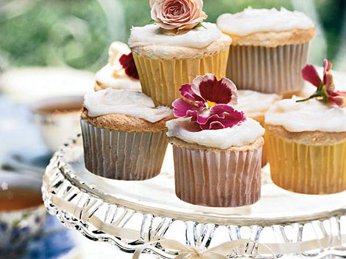 Sifting the flour mixture thoroughly three times incorporates the powdered sugar for a light, tender cupcake. Top with tiny edible pansy blossoms or rosebuds for decoration. Store extra cupcakes in an airtight container, ready to refill the platter as these delicious treats are sold.