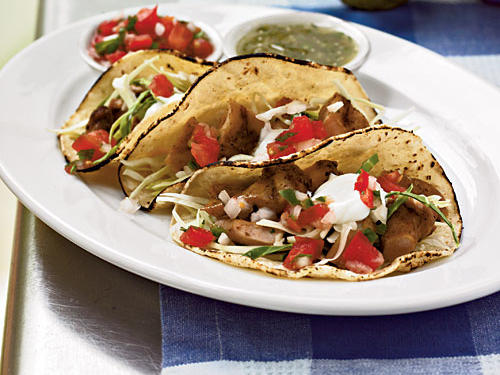 Dark-meat chicken is flavored with cumin, topped with sliced cabbage, and served in corn tortillas to give these tacos authentic flavor. You can grill the chicken a day or two ahead and reheat or use leftovers for the filling, but if you don't, try heating the tortillas on the grill; they'll have a nice toasted texture.
