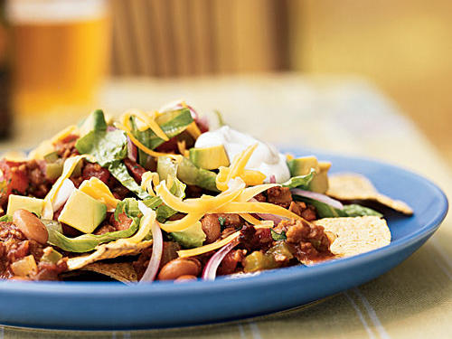 This dish might be a bit messy for a more formal party, but it's ideal for a gathering of close friends. The crunchy chips, loaded up with plenty of toppings, are fun to share. And if you don't tell the carnivores, they'll never know it's made with soy crumbles and not ground beef. You can easily vary the toppings to suit your taste―try adding jalapeño slices, or using pepper jack or queso fresco instead of the cheddar.