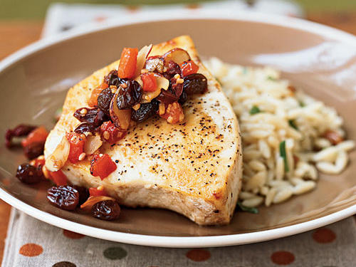 "Serving a ""special occasion"" fish like swordfish is an easy way to impress company, and this recipe impresses in other ways, too. The sweet-savory sauce, with raisins, olives, and almonds, is unexpected, unique, and delicious. And the whole dish takes just about 12 minutes to cook. Pork chops or tenderloin also make an excellent pair for the sauce if swordfish isn't your favorite."
