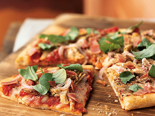 Leftover turkey provides the meaty backbone for this pizza, while prosciutto adds its salty savoriness and arugula contributes a slight bitterness and crunch. Fontina, though it's not a traditional pizza cheese, has a mild and nutty flavor that's nice here (but you can substitute mozzarella if you want). Prebaked pizza crusts are an effortless way to a quick pizza, but you can make the dough from scratch; stretch into a circle and bake at 500° for 8 minutes before using in this recipe.