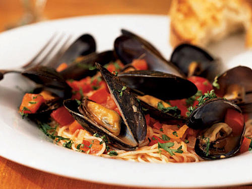 This simple dinner of angel hair pasta with mussels is a delicious way to enjoy fresh seafood.  Sweet red peppers help balance the naturally salty mussels, dry white wine, and the slightly acidic tomatoes.