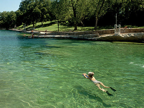 Austin's Barton Springs Pool features natural springs that maintain a refreshing 68-degree temperature year round.