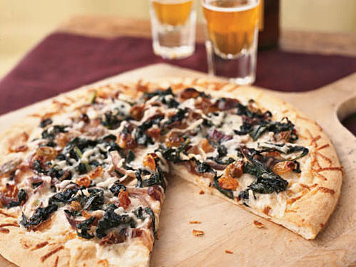 Anchovies and raisins, a popular eastern Mediterranean pairing, bring a salty sweetness to this calcium-rich pizza. Use any combination of cool-weather greens you like—collard greens, kale, or mustard greens.