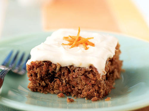 This lighter twist on traditional carrot cake features a tender cake packed with grated carrot, juicy pineapple, flaked coconut, and chopped pecans. Cream cheese frosting and a garnish of grated carrot top the cake.