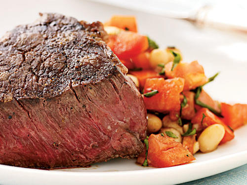 An easy-as-can-be preparation lets the ingredients speak for themselves here, so splurge on high-quality steaks and tomatoes. Beans and fresh tomato explode with flavor in a simple balsamic vinaigrette flavored with fresh herbs, while the steaks get a brief searing with only salt and pepper.
