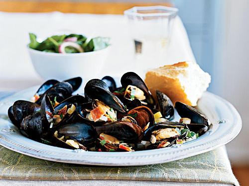 """Mussels take about 5 minutes to cook, but they impress everyone you serve. I love the mix of sweet and meaty flavors the cider and bacon add to briny mussels in this dish. My favorite way to eat them is straight out of the pot with my fingers―no silverware―just a loaf of bread and some paper towels.""