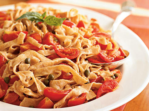 The nutty, slightly sweet flavor of whole-wheat flour is a tasty addition to a basic pasta recipe. Look for the smallest sweet tomatoes you can find for this simple sauce. Substitute grated orange rind for the lemon, if you prefer.