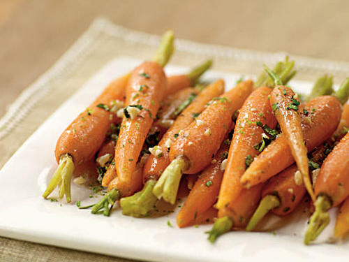 Steaming vegetables helps to retain all of the healthful water-soluble vitamins, and these carrots are no exception. The addition of the garlic-ginger butter gives an exotic flair to an otherwise classic dish.