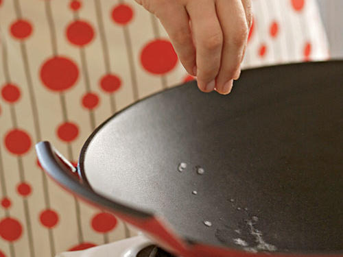 A hot wok with water droplets