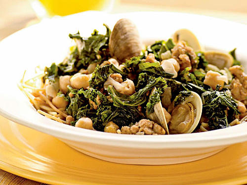 Get inspiration from the Portuguese and combine sausage, kale, and clams in one flavorful dish. Serve over fideos, a dish of thin noodles broken into small pieces, browned in the pan, and then simmered in broth until tender.