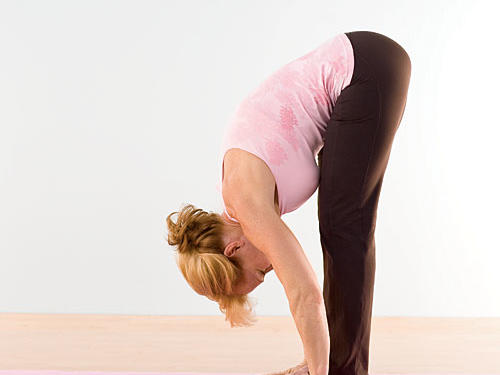 Bend forward from hips, keeping your back neutral (fairly straight with slight curve in lower back), and sweep arms down, allowing hands to rest on mat next to feet (as you become more flexible, try to rest your palms on the mat). If necessary, bend knees slightly to accommodate tightness in your hamstrings. Aim to bring chest to thighs.