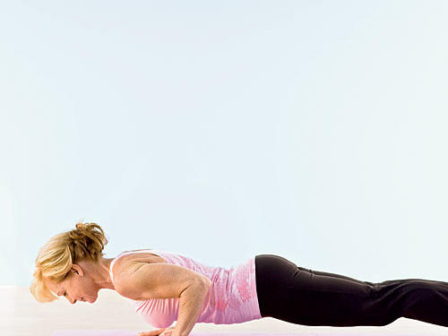 Step back with both feet into a push-up position, holding body weight ­between toes and hands. Arms should be straight beneath shoulders, palms flat on mat, with elbows pointing back and shoulders level. Lower your body ­toward the mat, allowing it to hover one to two inches above the mat. Maintain a straight line with your body as you breathe. Keep hips even without lifting or allowing them to sag or dip to one side. (If this position is too difficult to hold, decrease intensity by keeping arms fully extended straight below your shoulders rather than lowering body toward mat, or drop knees to the mat as if performing a modified push-up).
