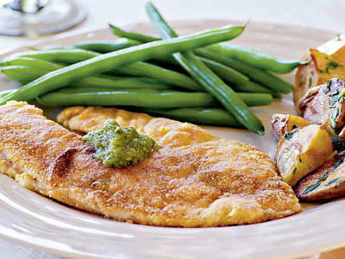 Tomatillo salsa adds a nice twist to this tilapia's cornmeal crust, while roasted potatoes and steamed green beans round out the plate.
