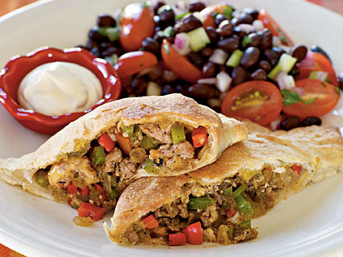 Spice up sandwich night with this Tex-Mex inspired favorite packed with ground turkey, fresh veggies, and spicy salsa. Thin-crust pizza dough serves as a blanket to wrap around your ground turkey scramble and keep all the delicious flavors in one enclosed bite. Serve immediately with sour cream on the side, or toss a few in the freezer to defrost the next time you're close on time. With 26 grams of protein, this calzone makes for a well-balanced, hearty option for dinner or lunch the next day. For an added kick, add jalapeños or poblano peppers to the filling and enjoy the heat.