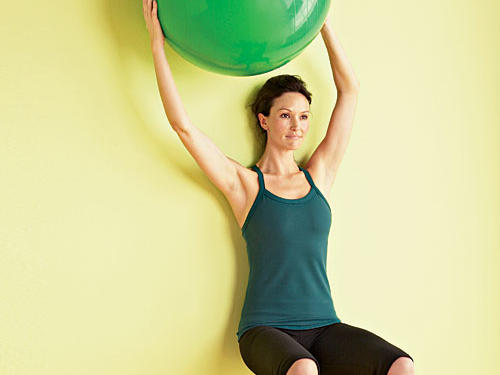 Target: Side and front absStart: Hold a nonweighted ball (such as an inflatable stability ball) in both hands, at chest level, and stand with back flat against a wall.Move: Slowly squat until thighs are parallel to the floor. Touch ball against wall over right shoulder, bring it back to center, then touch it to the wall over left shoulder for one rep. Keep back flat against the wall throughout the move, abs pulled toward spine, and knees in line with ankles; do not allow knees to push beyond toes.Repeat: Perform two sets of 10 to 12 reps with one minute of rest between sets.