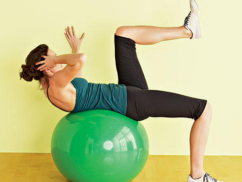 Target: Side and front absStart: Place a stability ball next to a sturdy object (a wall or bench) you can touch for balance, then lie with your back on the ball, feet flat on the floor. Lower back should be pressed into the ball with navel centered over ball. Hold wall with one hand; place other hand behind head.Move: Lift leg closest to wall off the ground, keeping knee bent. As you lift, twist upper body toward lifted leg, opposite arm and leg meeting above stomach. Use shoulder muscles to move your arm rather than pulling elbow forward. Lift knee toward chest, not chest to knee.Repeat: Perform 10 to 12 reps, then reposition and repeat on opposite side. Aim for two sets per side with one minute of rest between sets.
