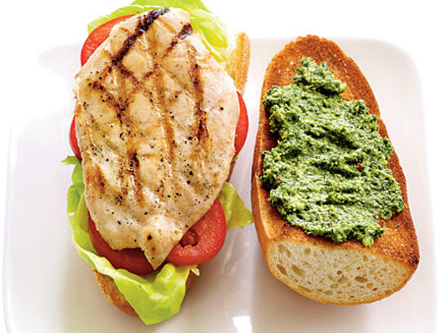 """Pesto perks up milder ingredients,"" Newgent says. Spread a tablespoon on a baguette topped with grilled chicken and tomato (shown here). Or pair pesto with fish. Put a dollop on a grilled fish fillet, like halibut, and serve with lettuce on a Kaiser roll."