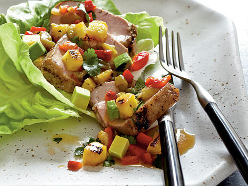 In a colorful mixture of flavors and textures, this pork salad features a mixture of grilled, spiced pork tenderloin combined with pineapple, bell pepper, chile, and avocado. The mixture is served in lettuce leaves and topped with a tangy vinaigrette.