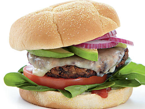 Serve this meatless black bean burger on a bun with hot sauce-spiked ketchup, spinach leaves, tomato, a slice of Monterey Jack cheese, avocado slices, and onion.