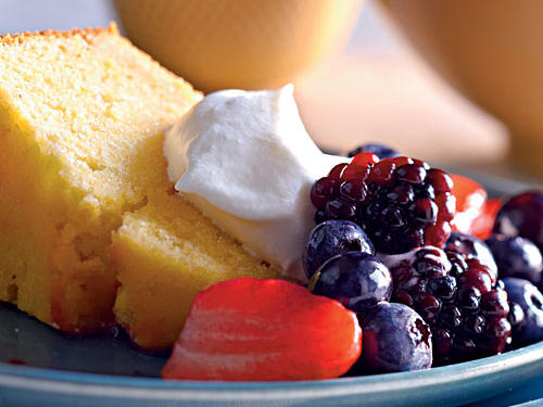 An assortment of sweet berries and freshly whipped cream tops Lemon-Cornmeal Pound Cake for a simple summer treat.