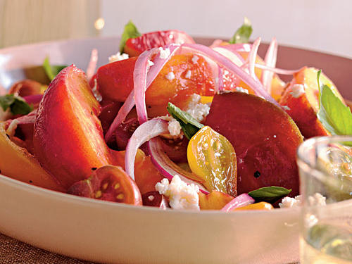 Simplicity has never looked so beautiful. A stunning combination of skin-on peaches and heirloom tomatoes of various colors, sizes, and shapes creates a sweet-savory salad that pairs well with grilled pork.