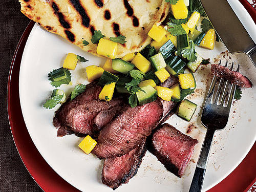 Grilled flank steak receives an extra punch of flavor when topped with fresh mango salsa. Serve with Garlic Flatbread.