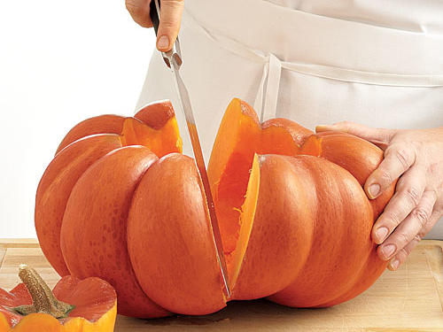 Step 3: Cut the pumpkin in half using a heavy chef's knife. Scrape the flesh with a spoon to remove any remaining fibers.