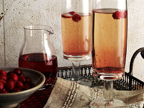Leftover cranberry sauce helps concoct a lightly sweet homemade cranberry liqueur in this twist on a classic French cocktail. Allow four days to steep the liqueur. Garnish with cranberries, if you like.