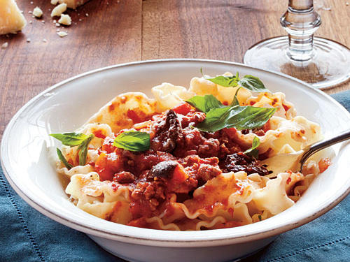 The meat sauce can be made ahead and then served over mafaldine, a flat noodle with ruffled edges. You can substitute spaghetti.