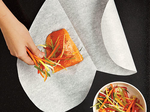 Arrange fish and veggies on one side of paper.