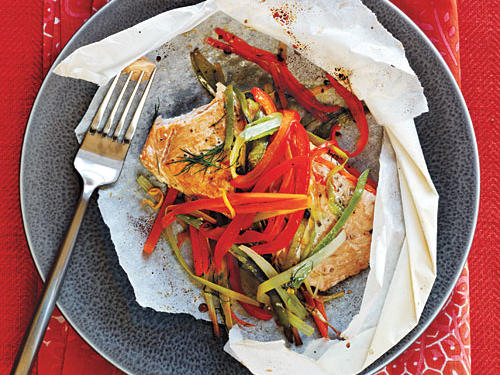 "Arctic char fillets topped with fresh, colorful vegetables are steamed in individual parchment pouches in this recipe, unwrapped by each diner at the table. ""Parchment packets allow the fish and vegetables to cook in their own juices and thus maintain the flavor of each ingredient,"" says recipe creater Jan Valdaz. Try this steaming technique at your home with our easy step-by-step guide."