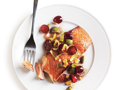 Serve this dish with pinot noir. Briny olives, sweet grapes, and rich salmon match well with the wine's balance of earthiness and acidity. Substitute picholine or other green olives, if necessary.