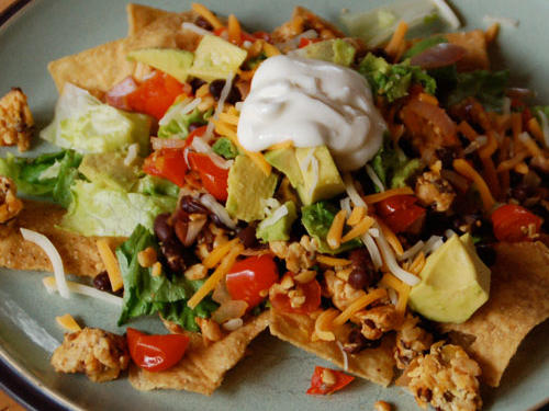 """When Kat made our meatless nachos, she used black beans instead of pinto, grape tomatoes instead of canned, diced tomatoes, and tempeh instead of faux meat crumbles. She also omitted cilantro and added lime juice. The nachos received a """"tastiness score"""" of 8/10."""