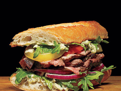 Piled high with steak and veggies, the real treat on this sandwich is the sauce, a pesto mayonnaise. Use sirloin for a more tender bite than you get with cuts like flank steak.