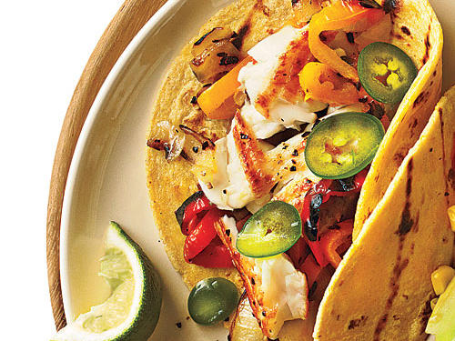 These low-fat tilapia tacos feature corn tortillas filled with tender pieces of sautéed fish, grilled onion, grilled bell pepper, and sliced jalapeño pepper. Slice the onion just before placing it on the grill. If given time to set, the onion rings will begin to separate and will not have good grill marks.
