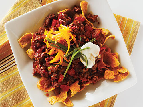 You may know it as a walking taco, taco in a bag, or Fritos chili pie—but this recipe is much lighter and much lower in sodium. Often served from concession stands at fairs, festivals, and sporting events, this crowd-pleaser usually involves splitting the bag of chips open, ladling chili into the bag, and then topping with cheese, onions, and other garnishes. When you make it yourself, and make smart choices like lean ground sirloin, lower-sodium beef broth, and lightly salted chips, you get to satisfy your cravings without having to feel guilty.