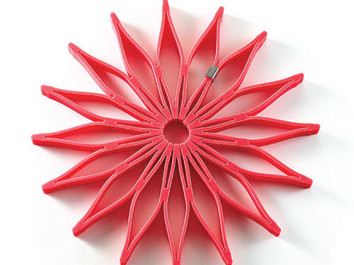 Hook the ends together, and a coaster-sized silicone square springs open to form a bloom-shaped trivet.