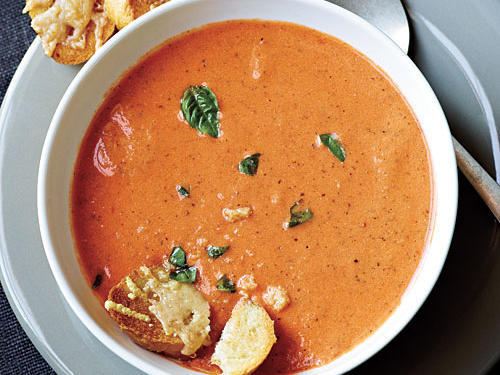 Bright, creamy tomato soup with a grilled cheese sandwich for dunking is a happy and comforting rite of childhood. This version's sure to please adults, too, with cheese toasts to replace the sandwich. Garnish with additional basil and a bit of crème fraîche, if desired.