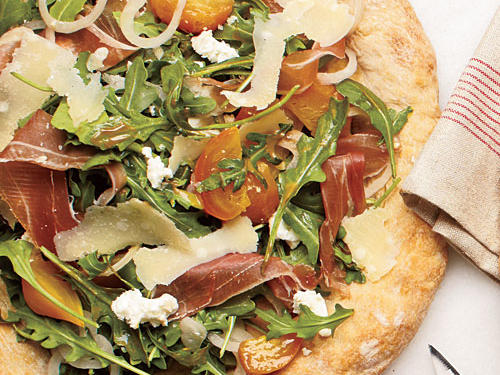 Golden beets adorn this pizza that's layered with arugula, crumbled goat cheese, and shaved Parmesan and prosciutto. Pre-made pizza dough provides a jump-start to this recipe and cuts down on prep time, making it an ideal weeknight dish.