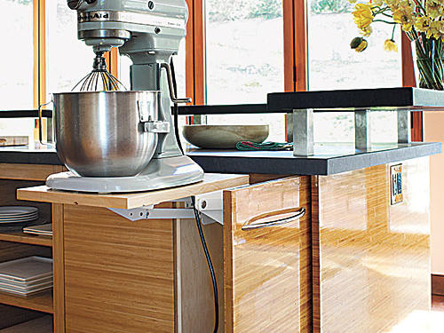 The unusual countertop appliance garages are replaced by cabinets sporting mechanisms that rise to the occasion when Hardie is in need of heavy or bulky appliances like her Cuisinart or KitchenAid stand mixer. Shelves mounted on special hardware pull up and out of the island cabinetry and lock into place at counter height.