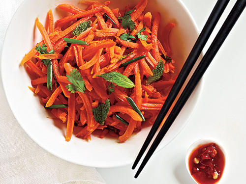 Some like cooked carrots, while others prefer them grated to make a crunchy salad. You can do either with this recipe—just toss steamed carrot coins with the dressing. The sweetness of the carrots is balanced by the fresh bite of the sambal oelek and chopped herbs.