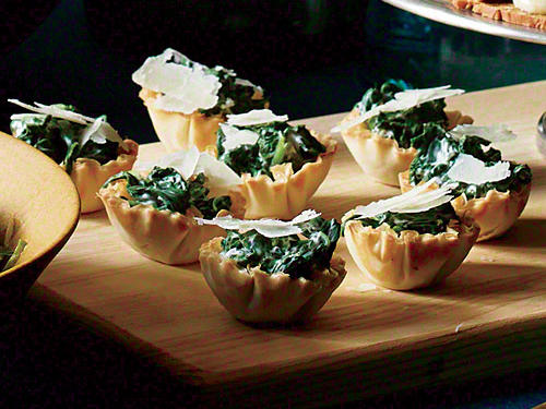 Turn a beloved side dish into a cute and savory appetizer. Frozen phyllo shells speed prep time, as does bagged baby spinach (rather than frozen). Toasting the phyllo cups keeps them crisp longer after being filled.