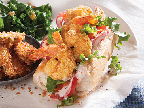 This dramatic po'boy makeover results from two strategies: a reasonable portion approach and oven-frying. Our sandwich is a wonderfully messy handful, just nowhere near a foot-long monster that in a traditional recipe can deliver an entire day's worth of calories and more than a day's worth of fat. Calorie cutting begins with keeping the shrimp and baked pickle chips away from the deep fryer, yet there's still the required crunch and yum because high-heat baking crisps things up mighty fine. You get a heap of garlicky kale on the side.