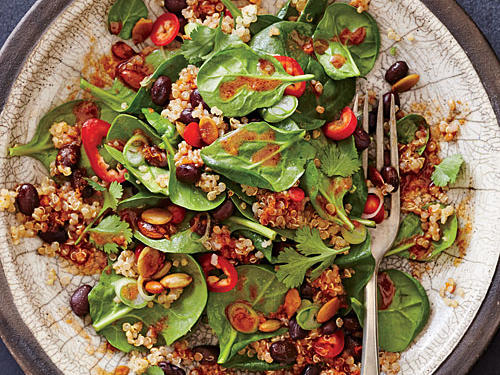 To make ahead, leave out the greens and keep the quinoa mixture covered in the refrigerator up to two days. Add spinach just before serving. To tame the heat, seed the chile or substitute chopped red bell pepper.