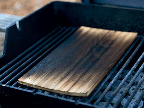 Grilling on a wood plank imparts mild, smoky flavor and keeps food moist thanks to damp smoke from the soaked wood. Planks suited for standard grills are widely available and come in a range of aromatic wood varieties. Alder, with its delicate flavor, pairs well with salmon and other seafood. Cedar, the most aromatic, works best with hearty foods such as chicken and pork. Hickory (think hickory-smoked bacon) loves beef, pork, and anything that can stand up to its strong, smoky aroma. Maple adds sweetness to ham, chicken, and fish. Wood planks can be found in barbecue and gourmet stores, seafood markets, and even your local supercenter.Wood Plank recipe: Alder-Planked Salmon in an Asian-Style Marinade