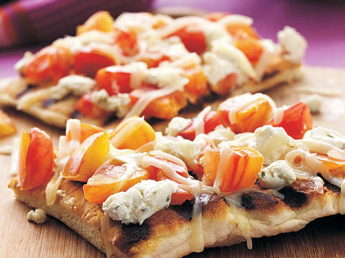 Summer-sweet heirloom tomatoes are the star of this recipe, complemented by mild and tangy goat cheese atop a crispy char-grilled pizza crust. If heirlooms are out of season, substitute just about any tomato.