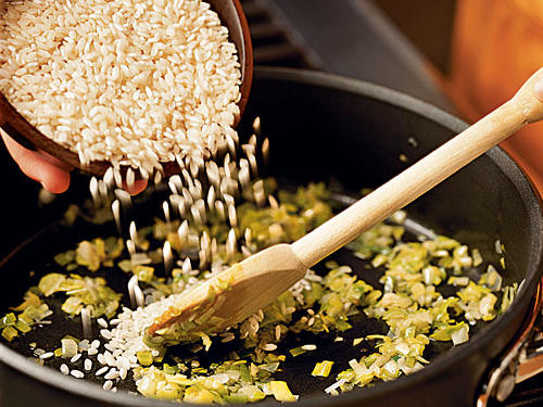 Sautéing the grain infuses it with flavors from the vegetables and helps the risotto reach a boil faster when the liquid is added.