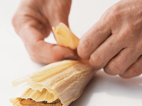 Fold bottom end of husk up and over tamale.